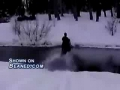 Snowmobile goes through a creek and into a tree