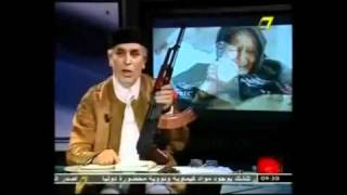 Libyan newsreader brandishes gun